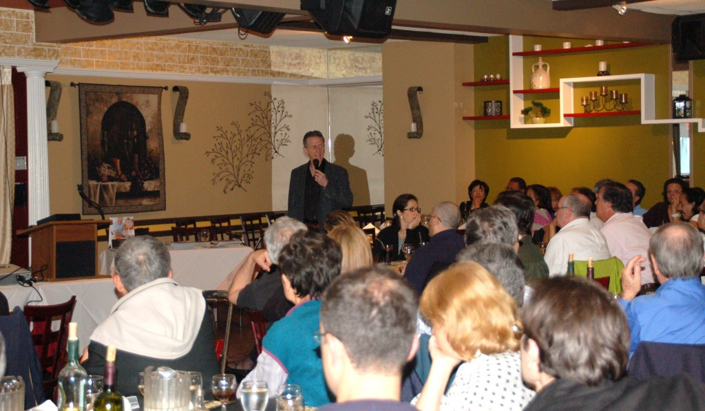Dr. Fialkoff giving a lecture to a large group of people during one of his courses