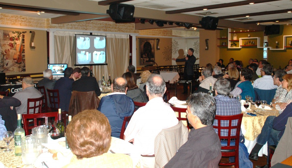 A zoomed out picture of Dr. Fialkoff explaining the x-rays, showing rows of people listening